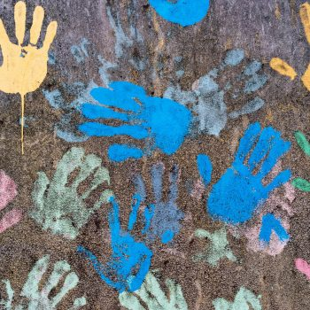Dark background with colorful handprints symbolising interracial friendship