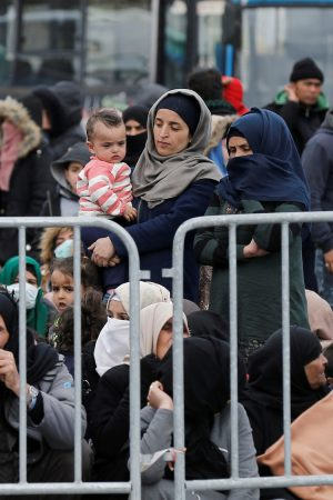 Migrants who arrived on the island of Lesbos in the past four days, are seen at the port of Mytilene, as they wait to board a Greek navy ship, in Mytilene